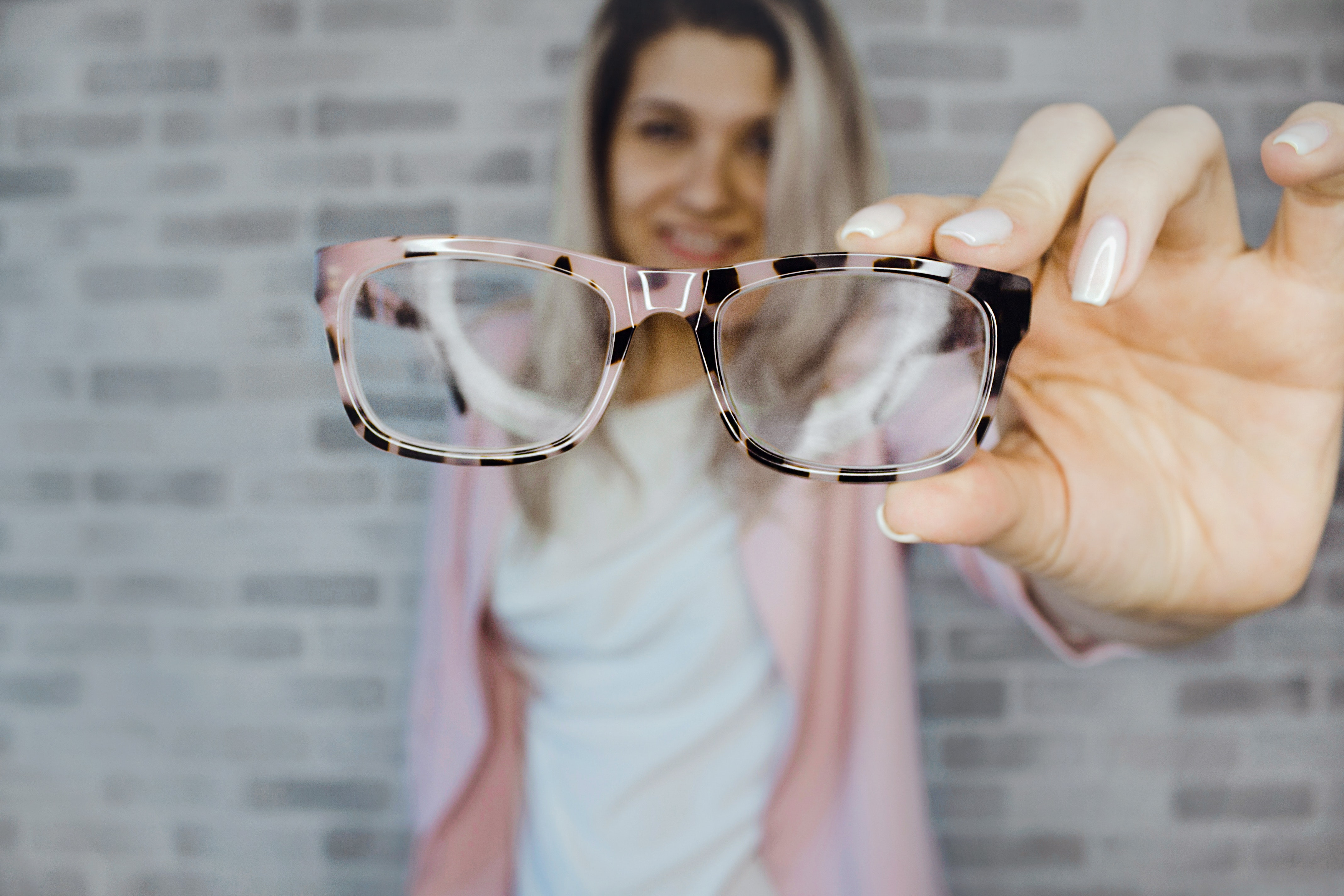 An image of a woman holding her glasses up to the camera.