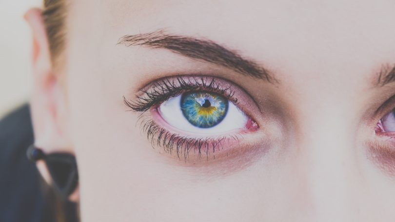 close up photo of womens blue right eye