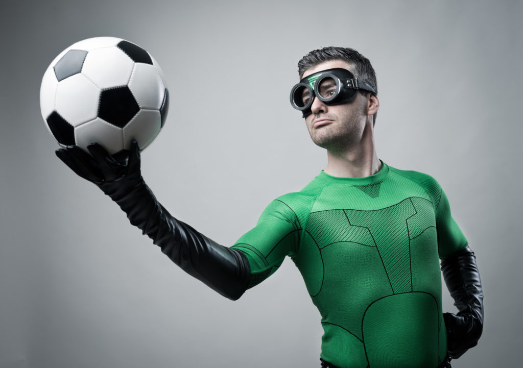 Confident superhero in green costume holding a soccer ball.