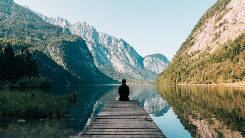 Man sitting on wharf looking at mountains