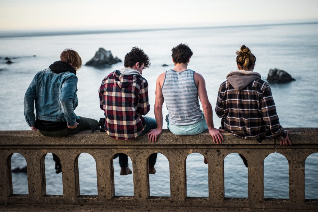 Teenagers sitting on fence overlooking water
