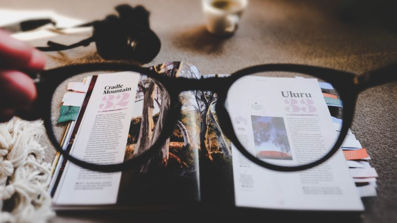 looking through glasses at a magazine
